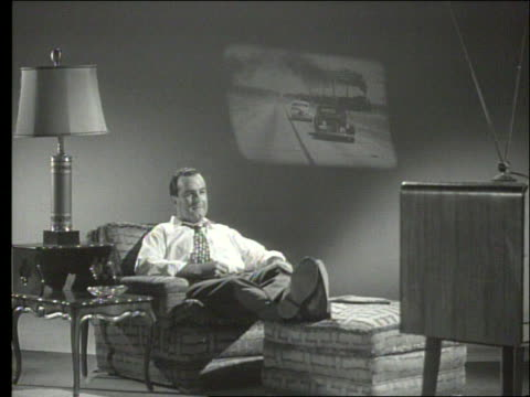 b/w 1950's man watches television then reads magazine / film projected on wall in background - black and white stock videos & royalty-free footage