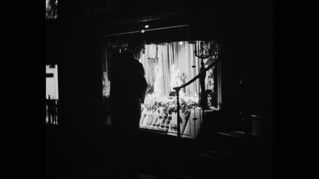 1950's - man window shopping at night, new york city, new york state, usa - 背景に人点の映像素材/bロール