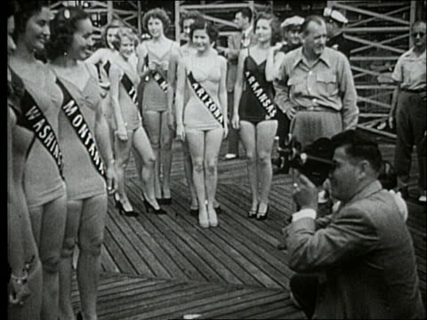 stockvideo's en b-roll-footage met b/w 1940's man with camera films miss america contestants wearing swimsuits / atlantic city - spelkandidaat