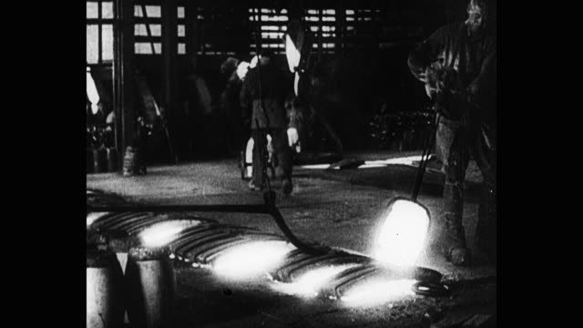 1920's medium shot of manual workers working in steel factory - molten stock videos & royalty-free footage