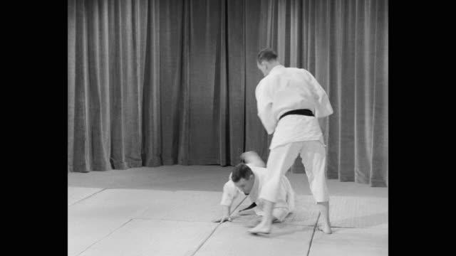 1960's - medium shot of men doing martial arts - カーテン レース点の映像素材/bロール