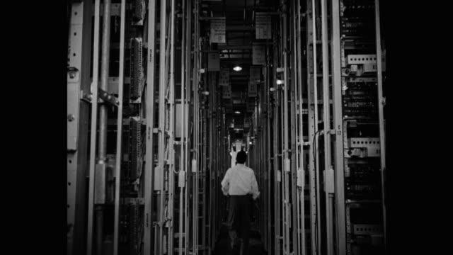 1950's - medium shot of men walking through telephone exchange aisle - kontrollrum bildbanksvideor och videomaterial från bakom kulisserna