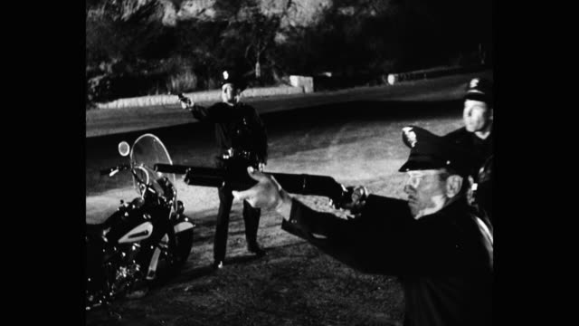 1950's - medium shot of policemen shooting guns at night - violenza video stock e b–roll
