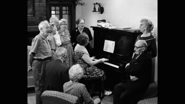 vídeos y material grabado en eventos de stock de 1960's - medium shot of senior people singing and playing piano in senior center - urbanización para jubilados