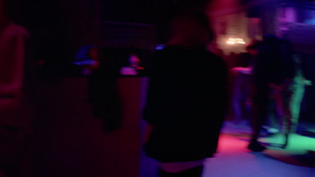 1980's medium shot pan people dancing under colored lights on dance floor in nightclub - 1985 stock-videos und b-roll-filmmaterial