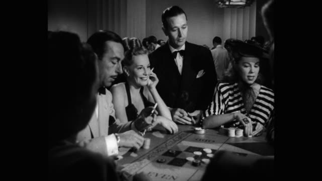 1940's - men and women placing chips on roulette table in casino - casino stock-videos und b-roll-filmmaterial