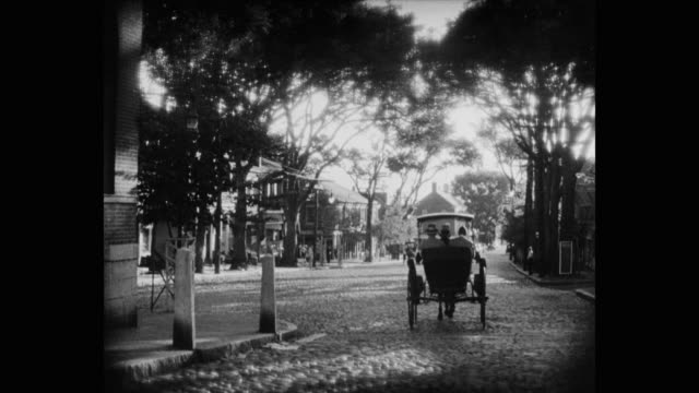 1930's - men traveling by horse carriage on cobblestone street in small town, united states - 植民地様式点の映像素材/bロール