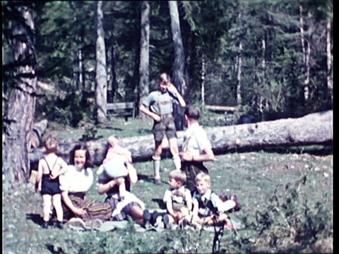 1940's montage family resting and playing among trees / tyrol, austria - austria stock videos & royalty-free footage