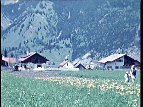 vídeos de stock, filmes e b-roll de 1940's ws pan mother and son walk among spring flowers in alpine meadow / tyrol, austria - áustria