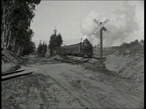 b/w 1910/20's motorcycle with sidecar crosses train tracks just before train comes / unreal newsreel - sidecar stock videos & royalty-free footage