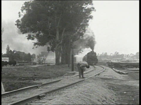 b/w 1910/20's motorcycle with sidecar picks up black man on train tracks just as train comes - sidecar stock videos & royalty-free footage