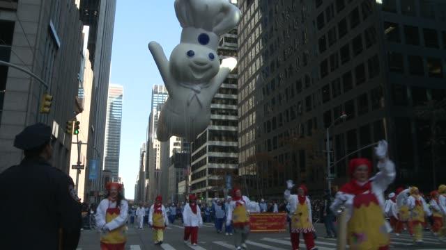 s mr. peanut and his nutmobile make its way down 6th avenue, followed by the morton salt float and the the pillsbury doughboy balloon / macy's... - 食品 ピーナッツ点の映像素材/bロール