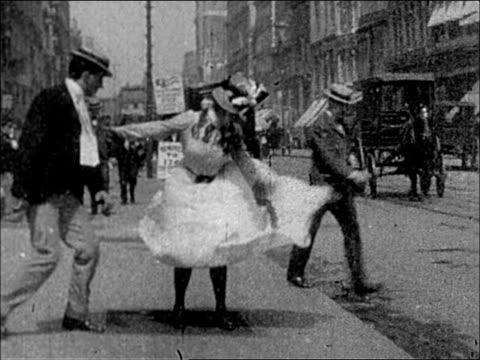 1900's NYC 23rd Street - woman's dress flies up as she walks over sidewalk vent