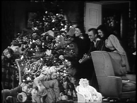 B/W 1930's or 1940's family hugging on Christmas morning by Christmas tree / SOUND