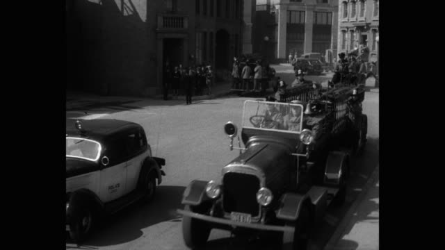 1940's - panning shot of fire engine with firefighters arriving at fire destructed area - 撮影現場点の映像素材/bロール