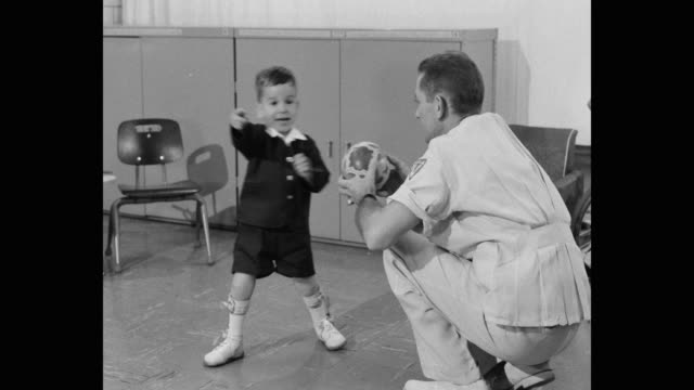 1960's - panning shot of man giving ball to disabled boy - polio stock videos & royalty-free footage