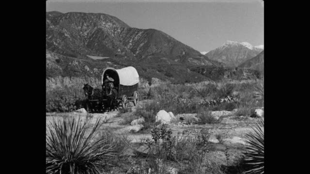 1950's panning shot of man riding covered horse drawn wagon through landscape against mountain range - wild west stock videos & royalty-free footage