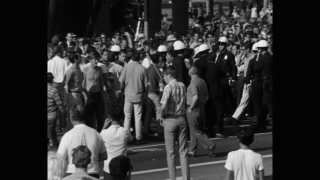 1960's panning shot of police officers walking with man during peace march on street, los angeles, ca, usa - talking politics stock videos & royalty-free footage