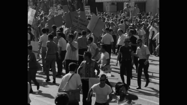 1960's panning shot of protestors fighting during protest on street, los angeles, ca, usa - placard stock videos & royalty-free footage