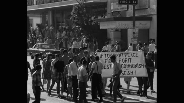 1960's panning shot of protestors protesting with banner on street, los angeles, ca, usa - talking politics stock videos & royalty-free footage