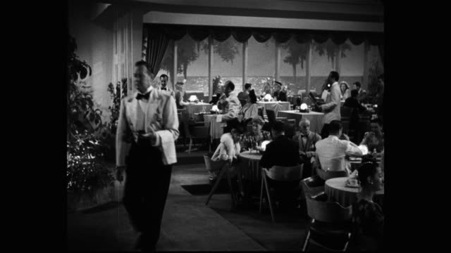 1940's panning shot of waiters serving diners in luxury restaurant - restaurant stock videos & royalty-free footage