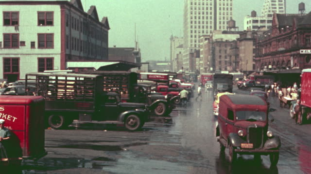 1940's pan of parked trucks, traffic + trucks unloading in meat packing district / nyc - film industry video stock e b–roll