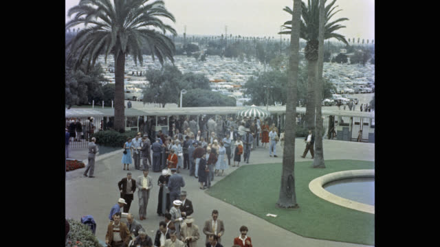 1950's - people arriving at hollywood park racetrack, inglewood, california, usa - pferderennbahn stock-videos und b-roll-filmmaterial