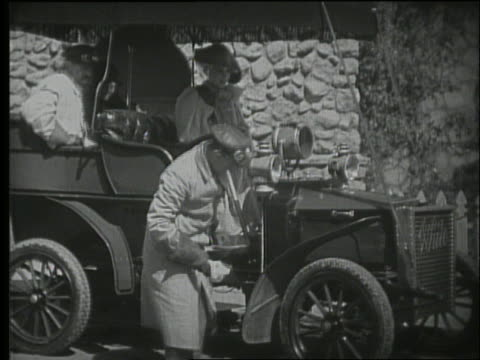 b/w 1900's people get into early car / drive off in smoke - 1900~1909年点の映像素材/bロール