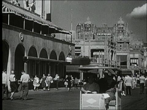 vídeos de stock, filmes e b-roll de b/w 1940's people walking and riding pushcart on boardwalk / buildings in background / atlantic city - atlantic city