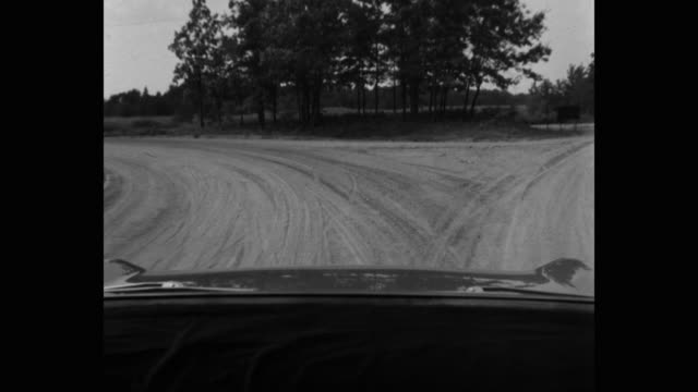 1950's point of view of car driving on country road passing through landscape - in movimento video stock e b–roll