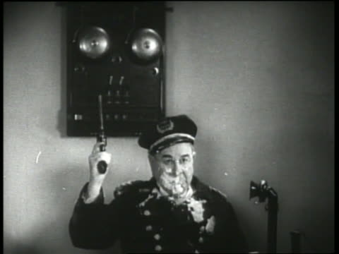 B/W 1930's policeman with cream on face shoots gun in air, part of ceiling falls on him