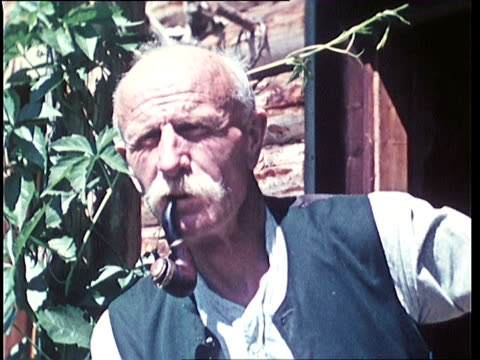 1940's CU Portrait of senior man with pipe in front of mountain cabin / Tyrol, Austria