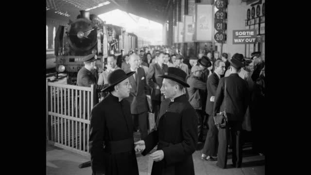 vidéos et rushes de 1950's - priests talking to each other at railway station platform while passengers leaving through gate in background, paris, france - prêtre
