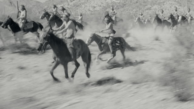 b/w 1800's reenactment crowd of native americans running on horses in desert / apache trail (1942) - ネイティブアメリカン点の映像素材/bロール