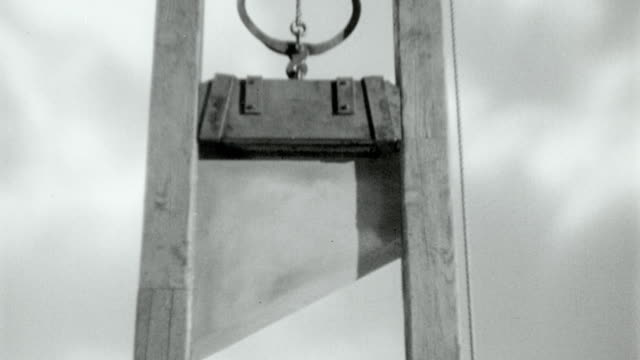 vídeos de stock e filmes b-roll de b/w 1700's reenactment low angle tilt up + zoom out of guillotine blade rising then being released / marie antoinette (1938) - guilhotina