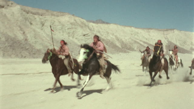 vidéos et rushes de 1800's reenactment tracking shot native americans on horses running in desert / escape from fort bravo (1953) - évasion