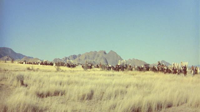 stockvideo's en b-roll-footage met 1890's reenactment wide shot pan people on horses, wagons + buggies speeding on plain in land rush / cimarron (1960) - koets