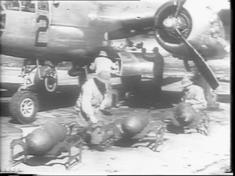 B52's sit on a landing strip / Men adjusts the bombs / Tail ends of the VT are tightened / Man loads and raises the VT fuse bombs onto the bomber