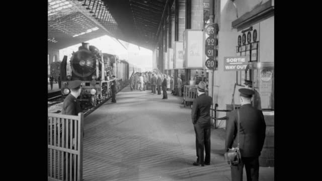 1950's - steam engine pulls into station as passengers wait on platform, france - zug mit dampflokomotive stock-videos und b-roll-filmmaterial