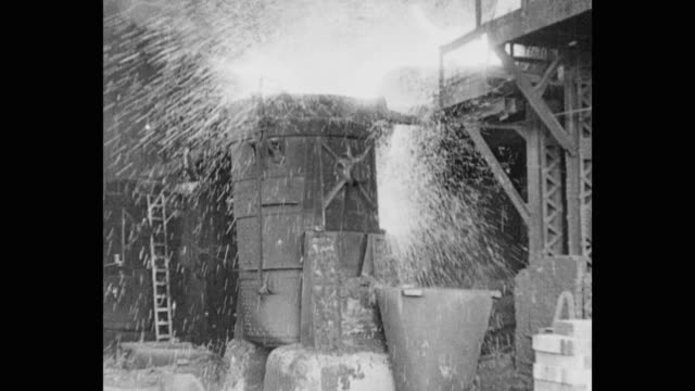 1930's steel factory - sparks fly as large cauldron fills with molten metal - steel mill stock videos & royalty-free footage