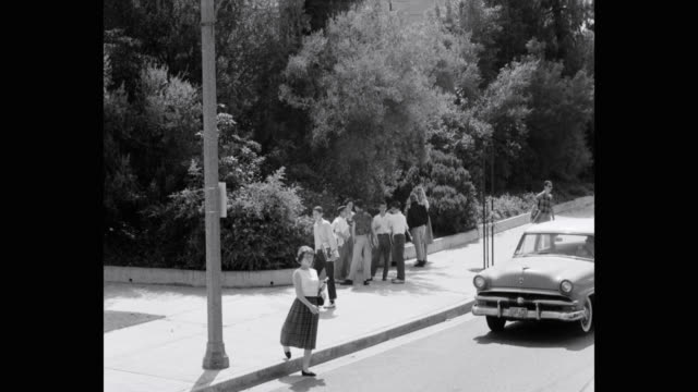 stockvideo's en b-roll-footage met 1950's students standing on sidewalk with cars driving on street, beverly hills high school, beverly hills, california, usa - beverly hills californië