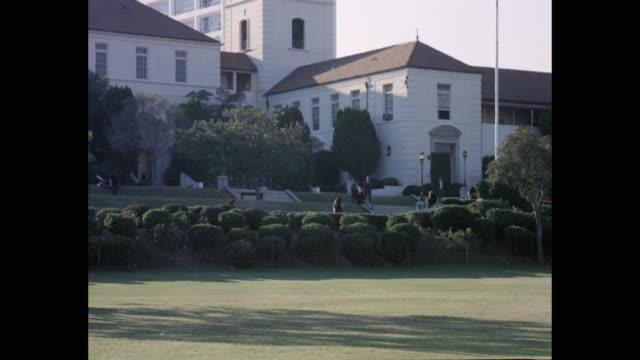 1970's students walking in beverly hills high school campus, beverly hills, california, usa - beverly hills california点の映像素材/bロール