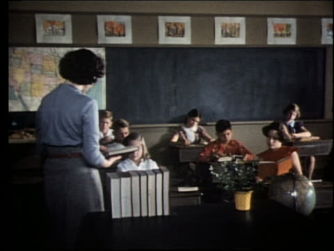 1960's teacher at front of classroom reading from book and talking to children / girl raises hand - textbook stock videos & royalty-free footage