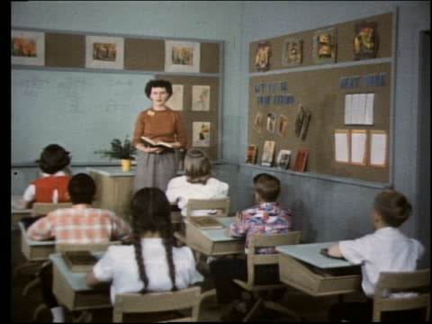 1960's teacher standing at front of classroom talking to children - klassrum bildbanksvideor och videomaterial från bakom kulisserna