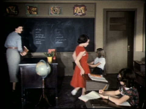 1960's teacher standing at front of classroom talking to children