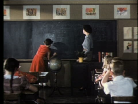 vidéos et rushes de 1960's teacher watches girl at chalkboard / girl sits down / classroom - passé