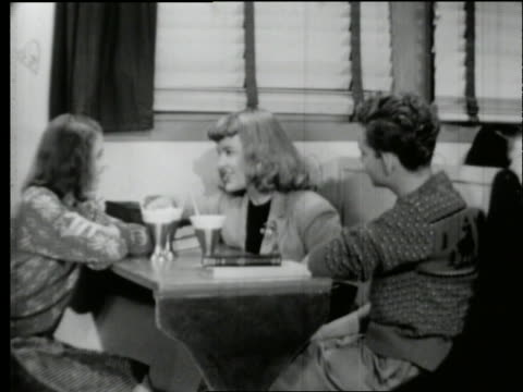 vidéos et rushes de b/w 1950's teen boy with sodas sits down at table with 2 girls talking in diner - homme dans un groupe de femmes