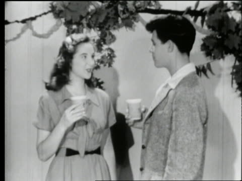 vidéos et rushes de b/w 1950's teen couple drinking from cups and talking at party - couple d'adolescents