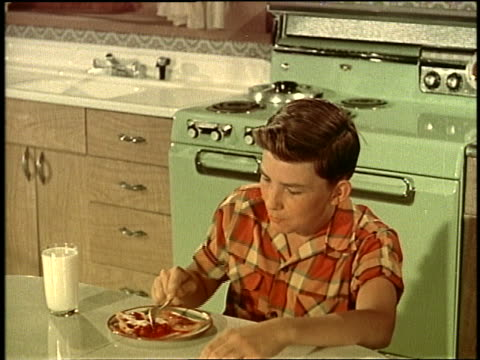 1950's teenage boy eating pie in kitchen