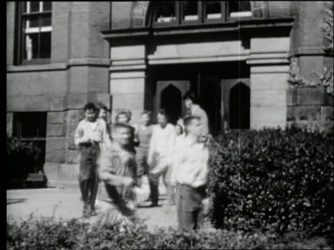 vídeos de stock, filmes e b-roll de b/w 1950's teenagers coming out of school building - aluno do ensino médio